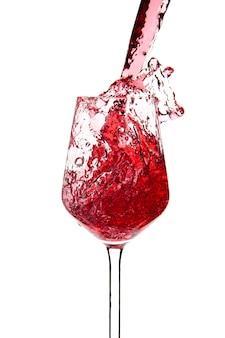 Le vin rouge se verse dans un gobelet en verre sur un fond blanc. boissons alcoolisées. photo de haute qualité