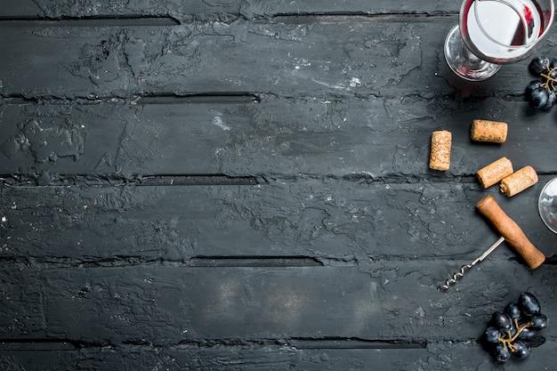 Vin rouge avec tire-bouchon. sur un noir rustique.