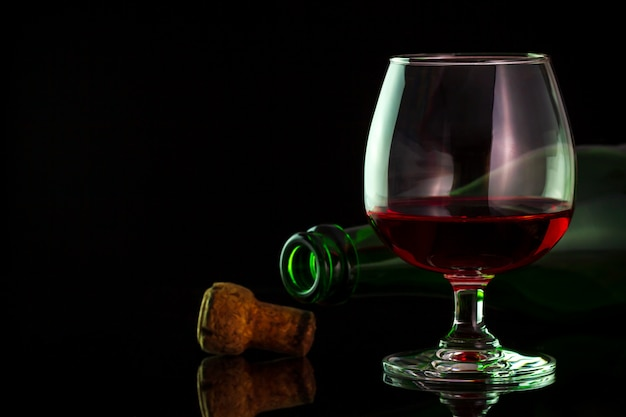 Vin rouge en verre et bouteilles sur la table dans le fond de l'obscurité.