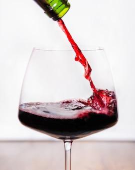 Vin rouge versé au verre, fond blanc