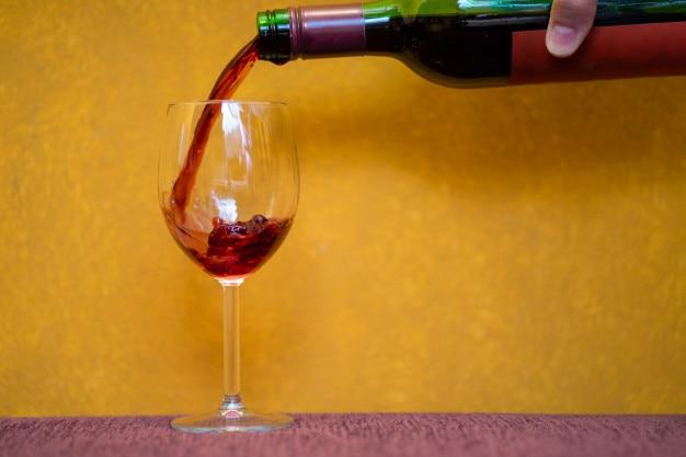 Vin rouge versé dans un verre sur fond jaune