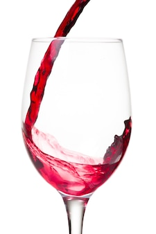 Vin rouge versé dans un verre isolé sur mur blanc