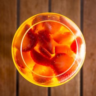 Vin de sangria dans le verre à vin et morceaux de fraise sur table en bois. vue de dessus.