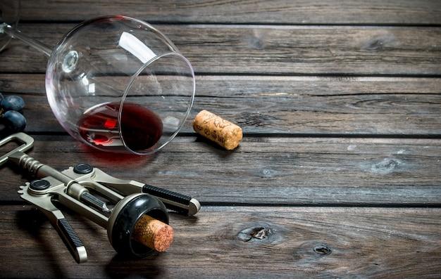 Vin. un verre de vin rouge avec des raisins et un tire-bouchon en bois.