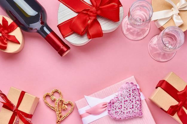 Vin, verres et coffret cadeau en forme de coeur avec un ruban rouge sur fond rose. carte postale de concept de saint valentin. vue de dessus.