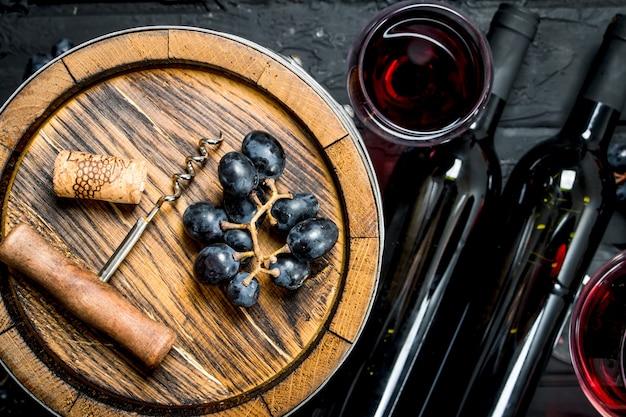 Vin. vin rouge avec des raisins et un vieux tonneau. sur un noir rustique.