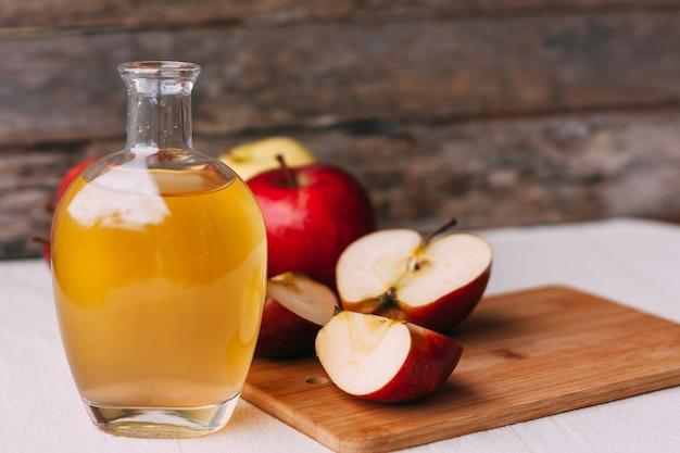 Vinaigre biologique de pomme dans un pichet en verre avec des pommes rouges et jaunes fraîches mûres sur fond de bois.