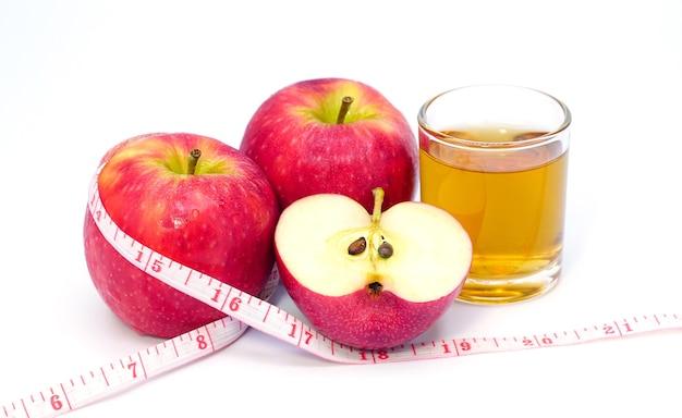 Vinaigre de cidre de pomme et jus de pomme avec ruban à mesurer sur fond blanc boisson saine