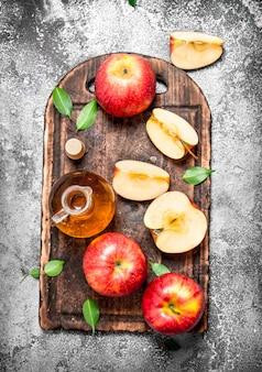 Vinaigre de cidre de pomme avec des pommes fraîches sur une planche à découper
