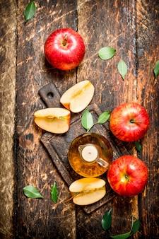 Vinaigre de cidre de pomme, pommes rouges sur table en bois.