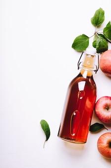 Vinaigre de pomme en bouteille sur une table en bois blanche avec des pommes et des feuilles.