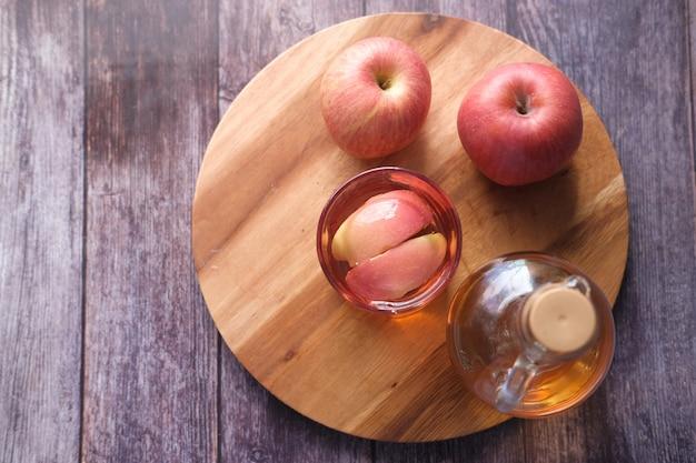 Vinaigre de pomme en bouteille de verre avec pomme verte fraîche sur table