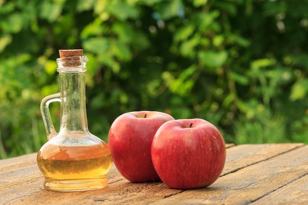 Vinaigre de pomme dans une bouteille en verre avec du liège et des pommes rouges fraîches sur de vieilles planches de bois rustiques.