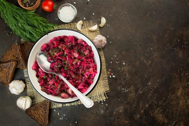 Vinaigrette aux herbes dans un bol blanc sur fond sombre. salade de betteraves. plat traditionnel russe. vue d'en-haut. plat végétarien. copiez l'espace. contexte alimentaire.