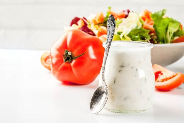 Vinaigrette ranch maison classique, avec des légumes frais sur une table en marbre blanc,