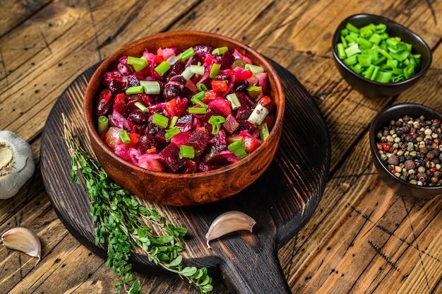 Vinaigrette de salade russe traditionnelle avec légumes bouillis, concombres marinés dans un bol. fond en bois. vue de dessus.