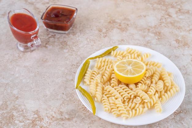 Vinaigrettes épicées et un repas fraîchement préparé sur une surface en marbre.