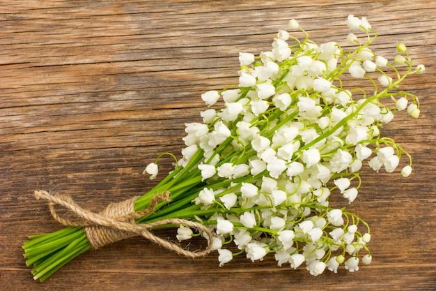 Vintage bouquet de fleurs sauvages, les lys parfumés blancs de la vallée sur une vieille planche de bois closeup