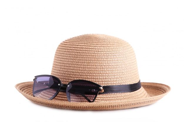 Vintage fabrique un chapeau de paille et des lunettes de soleil isolés sur blanc.