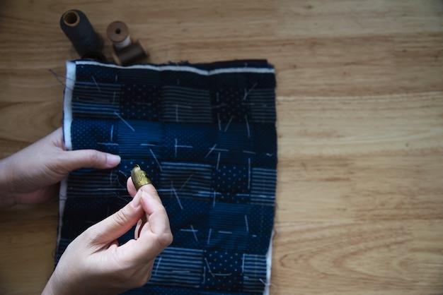 Vintage femme couture tissu à la main avec broderie mis sur la table en bois - personnes et concept de ménage bricolage à la main