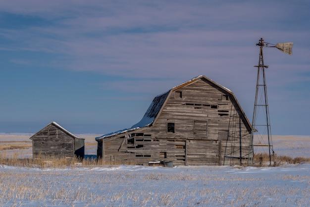 Vintage grange, bacs et moulin à vent entouré de neige sous un ciel de coucher de soleil rose en saskatchewan, canada