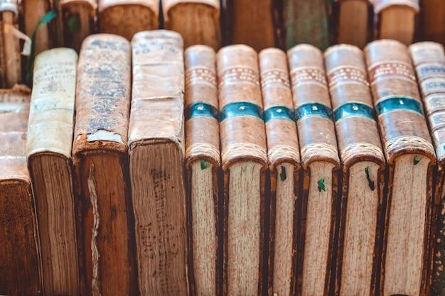 Vintage pile de livres anciens avec des couvertures brunes allongé sur une étagère au marché européen de la rue. pile de livres bruns d'occasion.