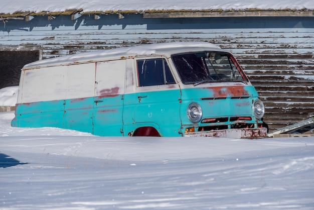 Vintage van abandonné bleu et blanc rouillant dans la neige