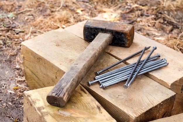 Vintage vieux marteau rouillé et clous allongés sur des barres de bois