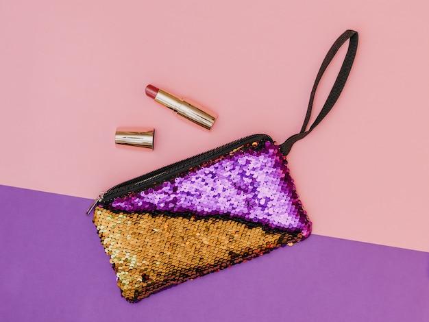 Violet avec sac à main d'or pour femmes avec rouge à lèvres sur une table bicolore. couleur pastel. mise à plat.