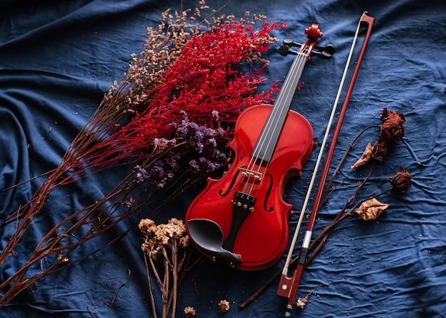 Violon et archet mis à côté de fleurs séchées