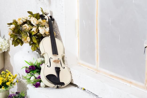 Violon blanc avec fleurs et salle blanche