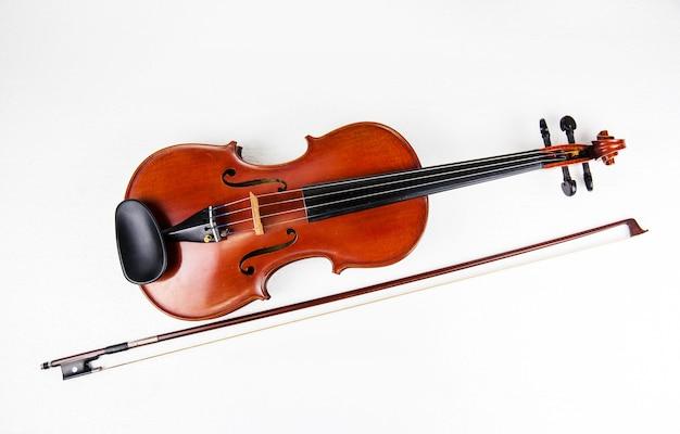 Le violon en bois et archet sur fond blanc