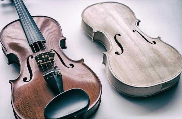 Violon brut mis à côté du violon terminé, montre la face avant du violon