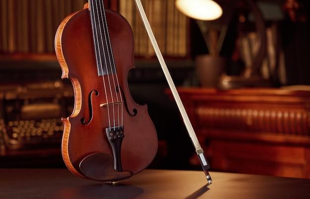 Violon dans un style rétro et archet, vue rapprochée, personne. instrument de musique à cordes classique, art musical, alto ancien