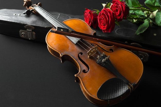 Violon et rose sur fond noir.