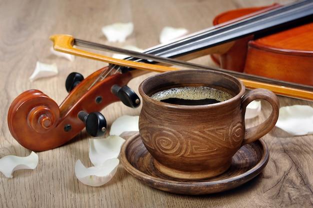 Violon et une tasse de café. café et pétales de rose