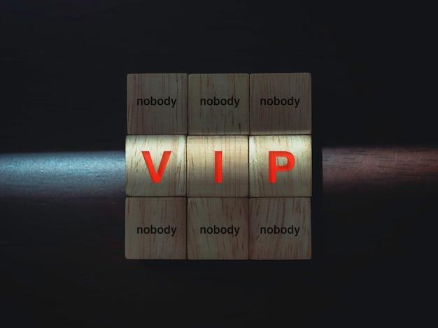 Vip et personne, mots sur des blocs de bois avec la lumière sur fond de bois sombre. privilèges portant atteinte aux libertés d'autrui et au concept des libertés civiles.
