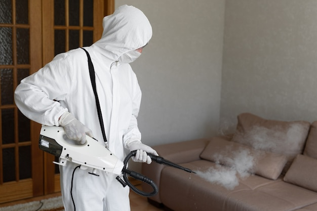 Un virologue en combinaison de protection contre les matières dangereuses procède à la désinfection des surfaces