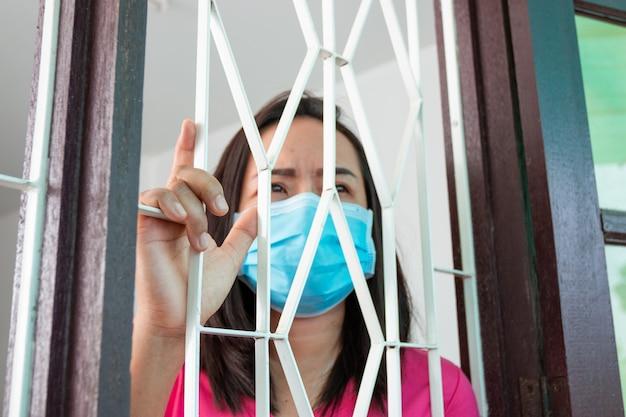 Virus corona covid-19, pendant sa détention à la maison femme masquée se sentir triste et seule dans la maison parfois, elle utilise son téléphone pour passer des appels vidéo avec des amis