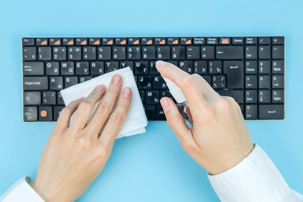Virus corona nettoyant et désinfectant votre espace de travail. lingettes désinfectantes pour essuyer la surface du bureau, du clavier, de la souris au bureau. arrêtez la propagation du coronavirus covid-19.