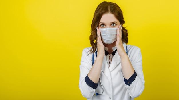 Le virus covid-19 effraie la femme médecin en état de choc portant un masque protecteur du coronavirus a l'air effrayée en se tenant le visage. sur fond jaune. espace libre de bannière