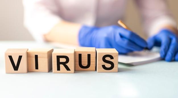 Virus de mot sur des blocs de cube et mains floues d'une femme médecin portant des gants de protection écrivant smth