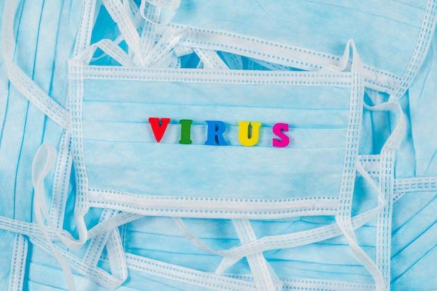 Virus de mot coloré sur les masques de protection. vue de dessus.