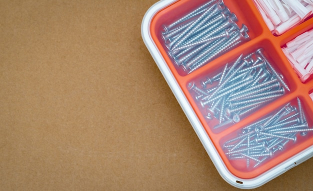 Vis en acier argenté et prise murale dans une boîte en plastique orange. boîte à outils vue de dessus sur fond de boîte de papier brun avec espace de copie. ensemble de vis et bouchon en plastique pour percer des éléments de mur et d'installation.