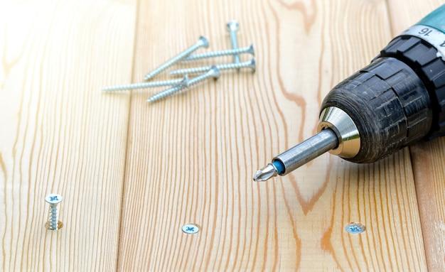 Vis et tournevis électrique sur un fond de planche de bois