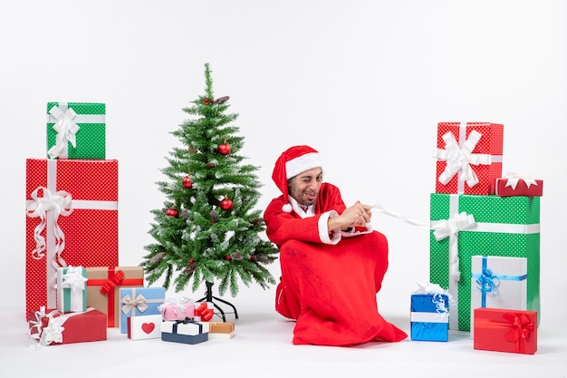 Visage aigre jeune homme habillé en père noël avec des cadeaux et arbre de noël décoré assis sur le sol sur fond blanc