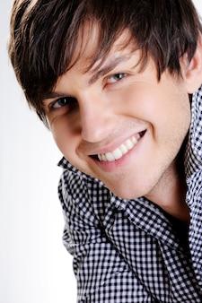 Visage d'un beau jeune homme heureux avec un sourire à pleines dents