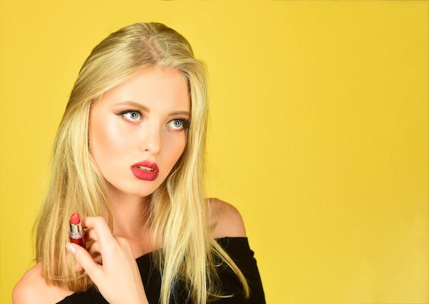 Visage de beauté et cheveux belles lèvres rouges blondes rouge à lèvres à la main maquillage de mode professionnel femelle