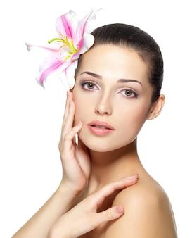 Visage beauté de la jeune femme avec fleur. concept de traitement de beauté. portrait sur fond blanc