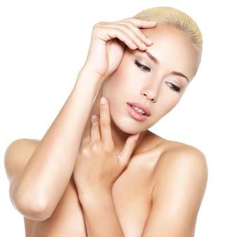 Visage beauté de la jeune femme jolie blonde avec les mains